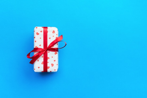 Present box of gift on blue colored table top view with copy space