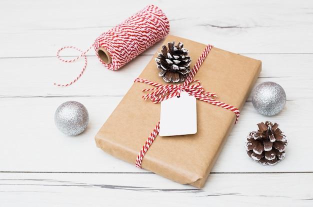 Подарочная коробка в обложке возле рождественских шаров и колышков