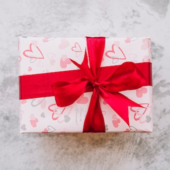 Present box in wrap with red ribbon