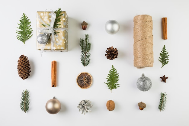 Present box near coniferous twigs, snags, bobbin of twists and ornament balls
