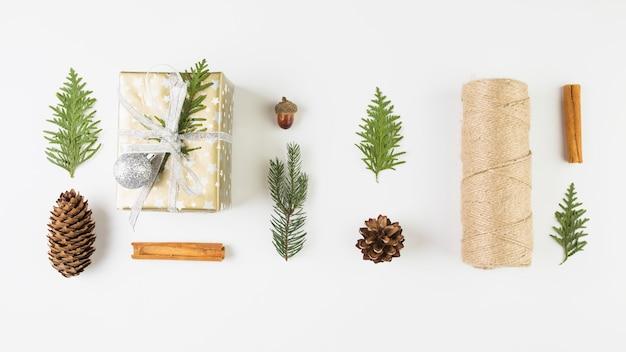 Present box near coniferous twigs, snags and bobbin of twists