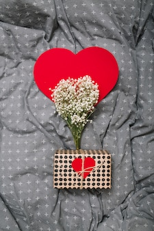 Present box near ornament paper heart and plants
