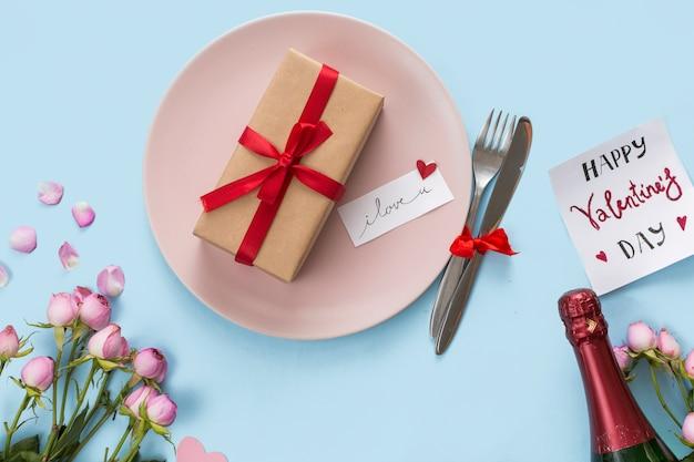 カトラリー、ボトルと花の間の皿の上のプレゼントボックス