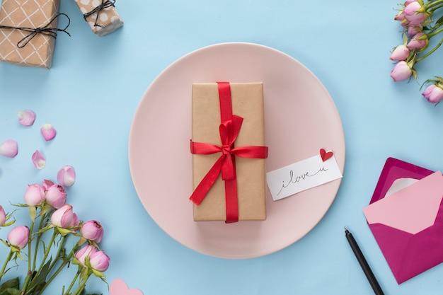 봉투와 꽃 사이의 접시에 선물 상자
