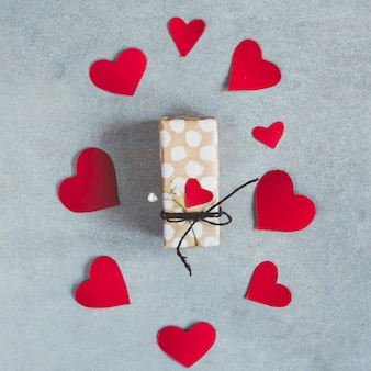 Present box between set of paper hearts