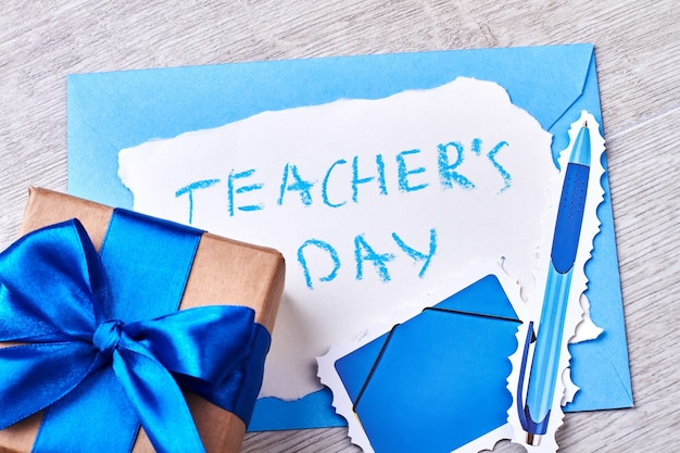 Present box with blue bow. teacher's day congratulation and gift.