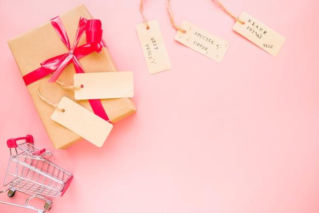 쇼핑 트롤리 및 판매 레이블 근처 활과 선물 상자