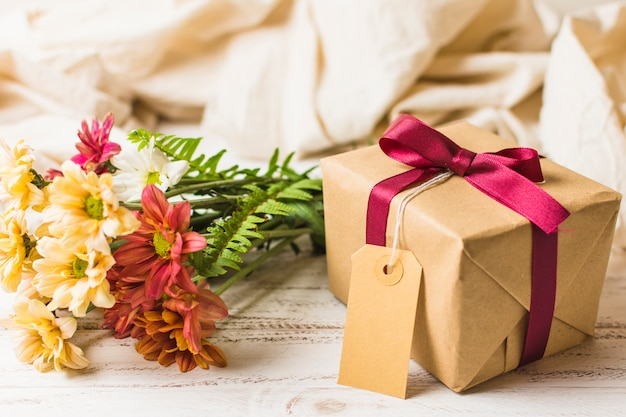 Present box with brown tag and flower bunch on table