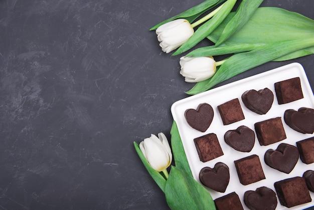 暗い背景にチョコレート菓子のハートとチューリップのプレゼントボックス。バレンタインデーの砂漠