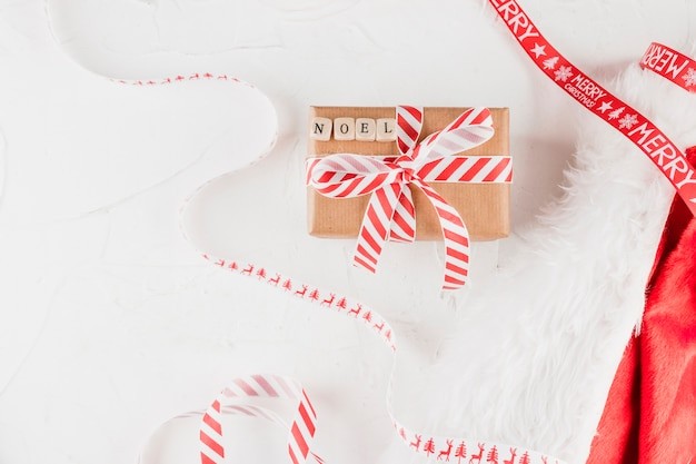 Present box with noel inscription near christmas tapes