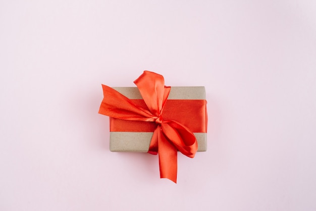 Present box with red bow on pastel pink background. flat lay, top view, copy space.