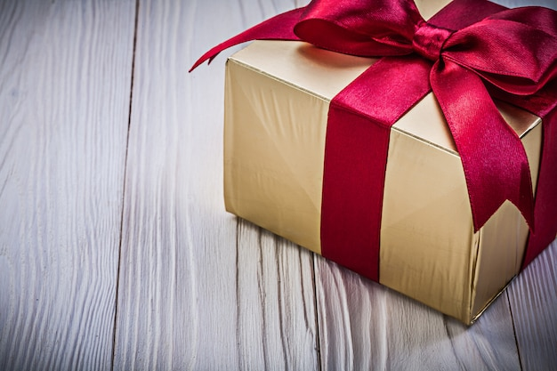 Present box with red bow on wooden board holidays concept