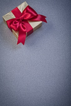 Present box with red knot on grey surface