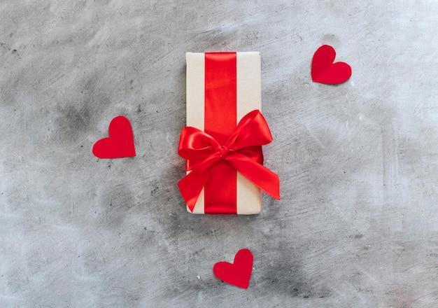 Подарочная коробка с красной лентой и сердечками