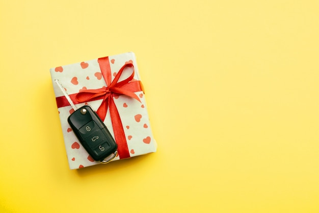 Present box with red ribbon bow, heart and car key on yellow colored