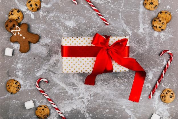Настоящая коробка с красной ленточкой лежит на сером полу с рождественскими печеньями, пряниками и красными белыми конфетами