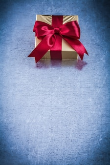 Present box with red ribbon on metallic holiday concept.