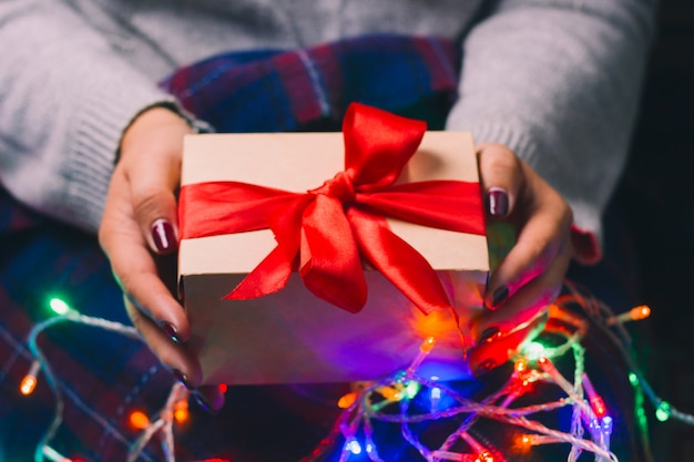 Present box with red satin ribbon in woman hands