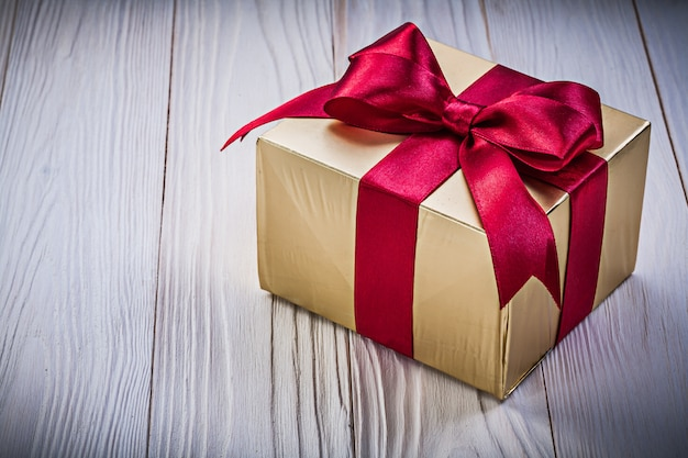Present box with red tape on wooden board holidays concept