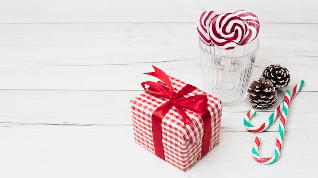 Present box in wrap near glass with lollipops and candy canes