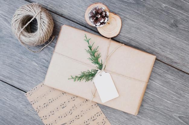 Present box in wrap near post card and bobbin of thread