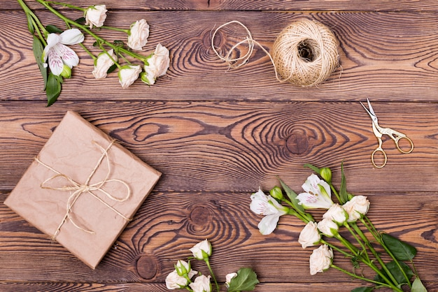 Present box wrapped in kraft paper and flower on wooden background