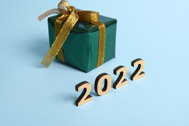 Present box wrapped in shiny glitter green gift wrapping paper and gold ribbon and bow on blue background with wooden numbers year 2022. christmas, new year concept. studio shot for ad with copy space