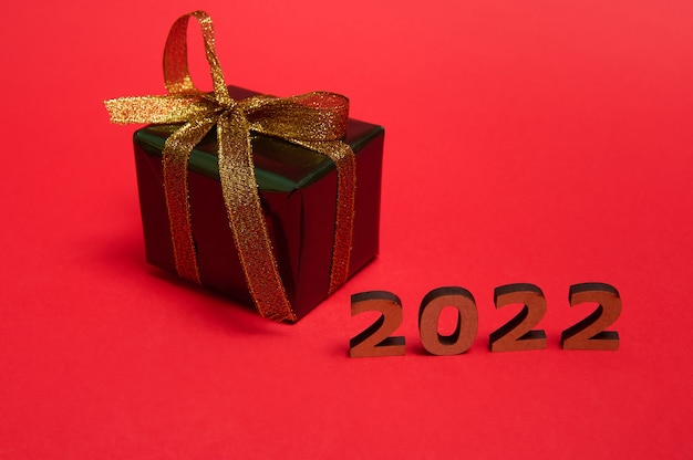 Present box wrapped in shiny glitter green gift wrapping paper and gold ribbon and bow on red background with wooden numbers year 2022. christmas, new year concept. studio shot for ad with copy space