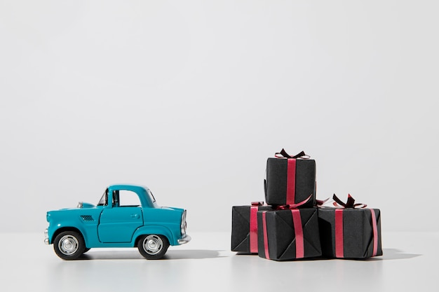 Подарочные коробки и синий автомобиль игрушки