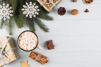 Present boxes in Christmas wrap near cup with marshmallows and fir branch