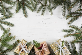 Present boxes in Christmas wrap near fir branches