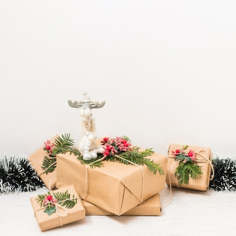 Present boxes near christmas deer and tinsel