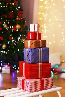 실내 크리스마스 트리 근처 나무 바닥에 있는 썰매에 상자를 선물하세요