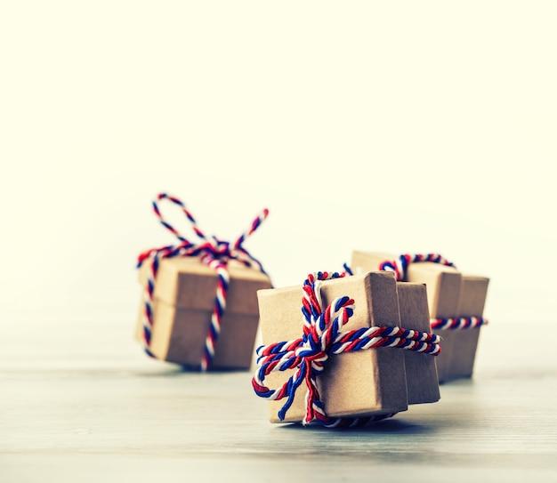 白い背中の背景を持つ木製の机の上に置かれた三色のより糸で結ばれたプレゼントボックス。