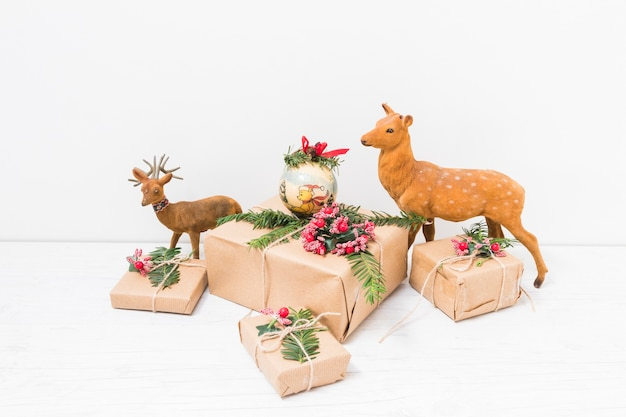 Present boxes with christmas ball near toy deer