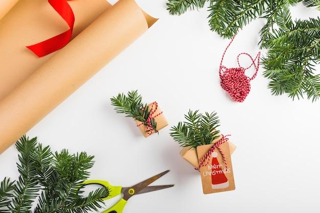 공예 종이 근처에 전나무 나뭇 가지와 스레드 선물 상자