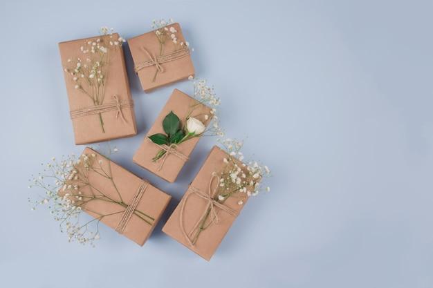 灰色のテーブルに花飾りのあるプレゼントボックス
