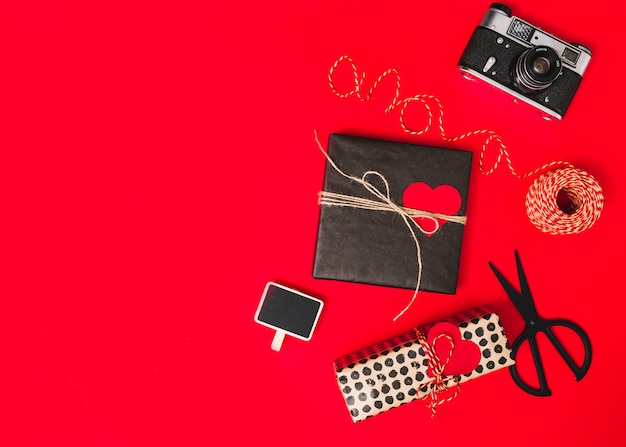 Present boxes with ornament hearts, camera, scissors and tablet