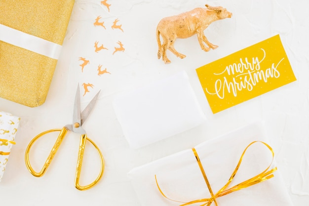 Present boxes in wrap near scissors, toy animal and post card