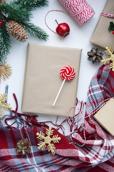 Present in brown craft paper, boxes, candy, plaid and christmas decoration on table. copy space. eco friendly new year concept