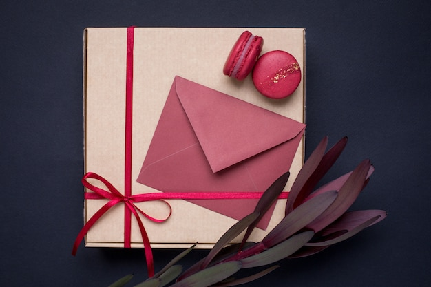 Present card and gift in box with satin ribbon on dark