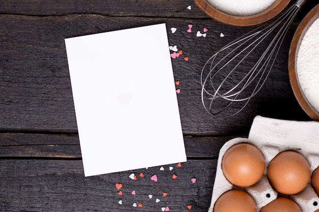 Present card , kitchen tools and hearts on wood