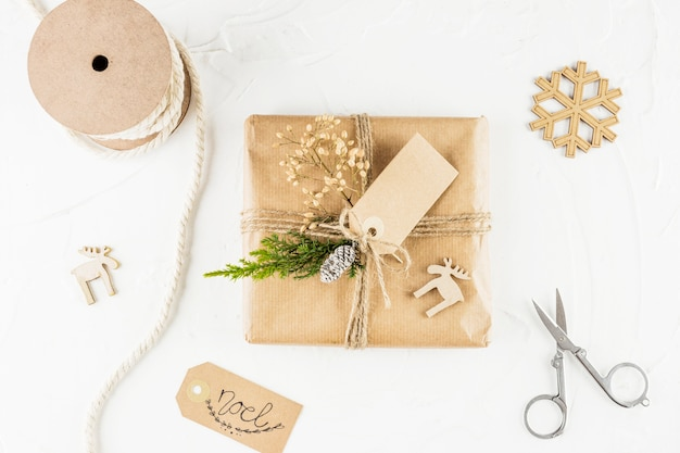 Present in craft paper with tag near scissors and snowflake