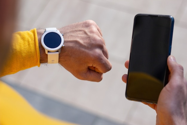 現在のデバイス。彼の黒い電話を持って、彼の白いモダンなスマートウォッチで時間を見て黄色いシャツを着た都会の男性の後ろからのクローズアップ。