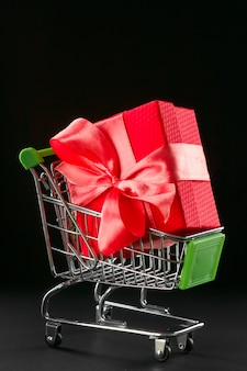 Present gift box in festive packaging with satin bow in the shopping basket.