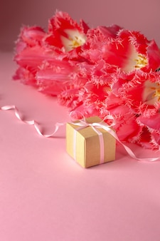 Present or gift box with beautiful bouquet of pink tulips flowers on pink surface.