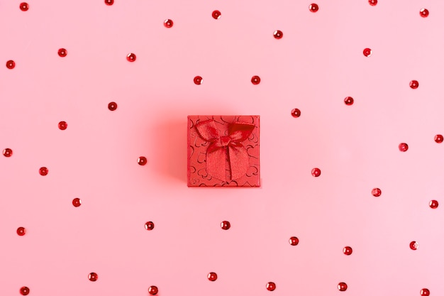 Present, gift box with red bow on pink background with tittle sparkles happy valentines day concept