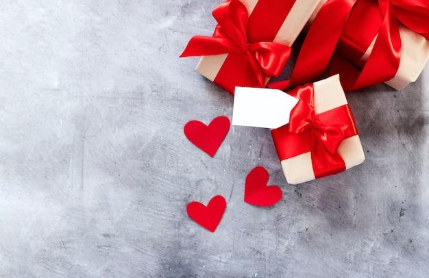 Присутствует подарочная коробка с красной лентой и сердечками.