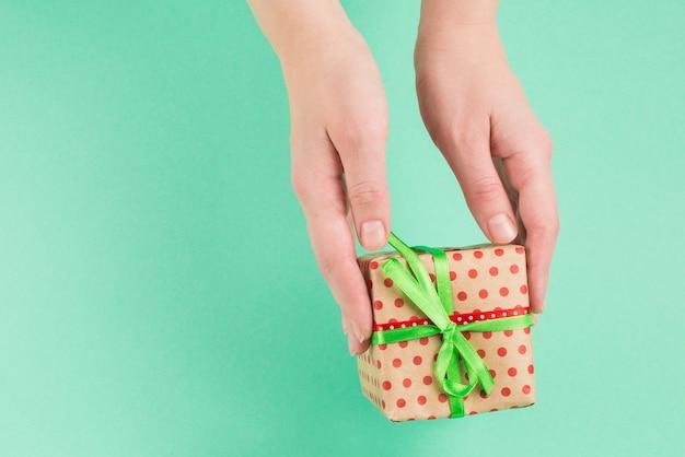 緑の背景に女性の手に存在します。スペースをコピーします。