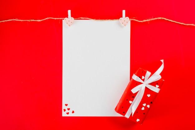 Подарок лежит возле листа бумаги и веревки